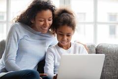 De glimlachende Afrikaanse moeder en jong geitjedochter heeft pret met laptop stock afbeeldingen