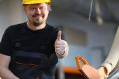 De glimlachende arbeider in gele helm toont teken bevestig royalty-vrije stock foto's