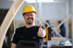 De glimlachende arbeider in gele helm toont teken bevestig stock foto