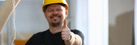 De glimlachende arbeider in gele helm toont teken bevestig stock foto's