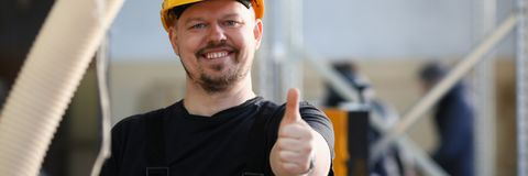 De glimlachende arbeider in gele helm toont teken bevestig royalty-vrije stock fotografie
