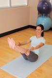 De glimlachende atleet in yogaboot stelt stock foto's