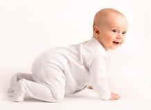 De glimlachende baby kruipt Stock Foto's