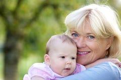 De glimlachende baby van de grootmoederholding Stock Foto