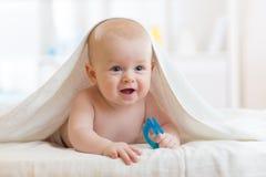 De glimlachende babyjongen na douche of het bad met teetherstuk speelgoed behandelde handdoek in kinderdagverblijf Gezondheidszor stock afbeelding