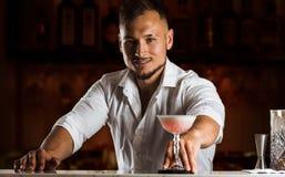 De glimlachende barman geeft de gast een elegante cocktail in lange glas stock foto
