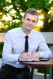 De glimlachende bedrijfsmens werkt van zijn bureau bij openlucht bij de koffie Stock Afbeeldingen