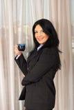 De glimlachende bedrijfsvrouw drinkt een koffie Stock Fotografie