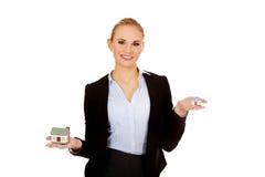 De glimlachende bedrijfsvrouw vergelijkt twee huismodellen Royalty-vrije Stock Foto
