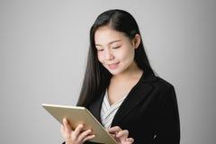 De glimlachende bedrijfsvrouwen houden tablet en het gebruiken van online toepassingen stock afbeelding