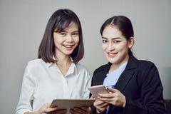 De glimlachende bedrijfsvrouwen houden tablet en het gebruiken van online toepassingen stock afbeeldingen