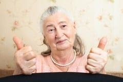 De glimlachende bejaarde van het portret Wijfjes met positieve emotieshanden die teken van o.k., o.k., duim tonen, succes stock afbeelding