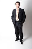 De glimlachende bevindende witte zakenman in kostuum met dient zakken in stock fotografie