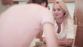 De glimlachende blondevrouw zit bij lijst in keuken met de jonge mens die van haar bedrijf lid worden stock video