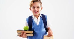 De de glimlachende boeken en lunch van de schooljongenholding stock video