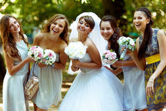 De glimlachende bruid stelt met gelukkige bruidsmeisjes met bouqets in hun Stock Fotografie
