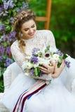 De glimlachende bruid zit als voorzitter Stock Afbeeldingen