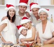 De glimlachende cakes van Kerstmis van het familiebaksel Stock Fotografie