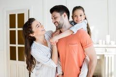 De glimlachende dochter van de vaderholding met dichtbij langs moeder royalty-vrije stock fotografie