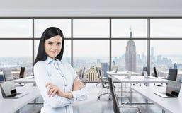 De glimlachende donkerbruine bedrijfsdame met dwarshanden bevindt zich in een modern panoramisch bureau in de Stad van New York P Royalty-vrije Stock Afbeeldingen