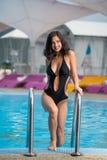 De glimlachende donkerbruine vrouw in het elegante zwarte zwempak met goed gevormd lichaam stelt dichtbij het zwembad bij de toev Royalty-vrije Stock Foto's