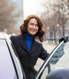 De glimlachende Europese vrouw op middelbare leeftijd zit in de auto royalty-vrije stock foto's