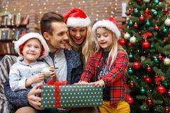 De glimlachende familie met Kerstmis stelt voor Stock Fotografie