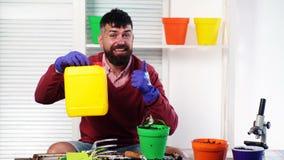 De glimlachende gebaarde mens houdt een plastic bus in zijn handen, en in een andere hand houdt een pot met een installatie Het t stock video