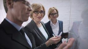 De glimlachende gelukkige bedrijfsvrouw die met partnerplannen bespreken, keurt de overeenkomst goed stock footage