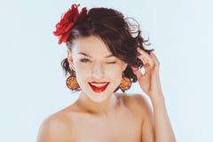 De glimlachende gelukkige jonge vrouw knipoogt Stock Afbeelding