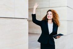 De glimlachende gelukkige onderneemster kleedde zich formeel, houdend in handen moderne tabletcomputer, die met haar hand golven  stock afbeeldingen
