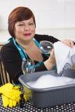 De glimlachende glazen van de huisvrouwen schoonmakende wijn Stock Afbeeldingen