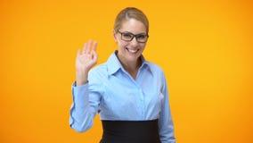 De glimlachende golvende hand van de bureaumanager, vriendschappelijke bedrijfarbeider, vrouwelijke collega stock footage