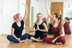De glimlachende groep meisjes die hoogte vijf geven bij groepsklasse, paste sportieve jonge vrouwen aansluit zich bij handen gelu stock fotografie