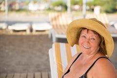 De glimlachende Hogere vrouw die hoed dragen bij strand sunbed  Stock Foto