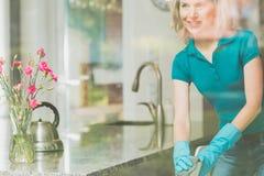 De glimlachende huisvrouw maakt stoel schoon royalty-vrije stock afbeelding