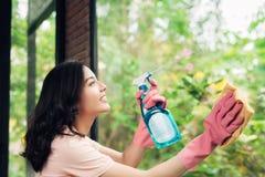 De glimlachende jonge Aziatische vrouwenhuisvrouw wast een venster stock foto's