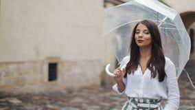 De glimlachende jonge donkerbruine vrouw in kleding loopt met paraplu langs de straat van een oude stad Het lopen onder de regen stock video