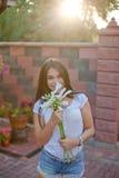 De glimlachende jonge donkerbruine vrouw met bloemen in werf van haar residen Stock Afbeeldingen