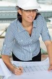 De glimlachende jonge ingenieursvrouw herziet een tekening Royalty-vrije Stock Foto's