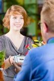 De glimlachende Jonge Klant die van de Bloemwinkel Elektronische Coupon gebruiken stock afbeeldingen
