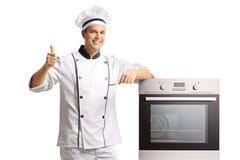 De glimlachende jonge mannelijke zich naast een oven bevinden en chef-kok die beduimelt omhoog geven royalty-vrije stock foto
