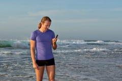De glimlachende jonge mens leest sms op strand Stock Foto