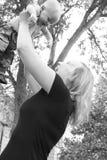De glimlachende jonge moeder houdt haar baby in de lucht tegen in openlucht royalty-vrije stock afbeeldingen