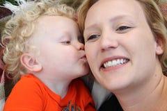 De glimlachende jonge moeder krijgt kus van haar weinig BO Stock Afbeelding