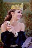 De glimlachende jonge vrouw kleedde zich als koningin die een appel houden Royalty-vrije Stock Foto