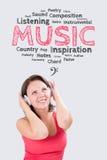 De glimlachende jonge vrouw luistert aan muziek onder de emoties bub Stock Afbeeldingen