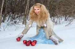 De glimlachende jonge vrouw met ongebruikelijk kapsel stelt met appelen Stock Afbeeldingen