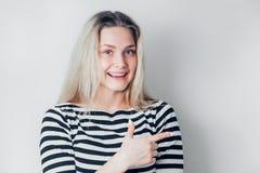 De glimlachende jonge vrouw richt weg een vinger royalty-vrije stock afbeeldingen
