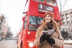 De glimlachende jonge vrouw in warme kleren en een smartphone in haar handen luistert aan muziek in de hoofdtelefoons en kijkt zi stock foto's